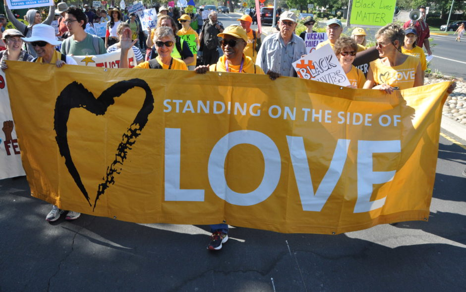 """UU community marches with sign """"Standing on the Side of Love"""""""